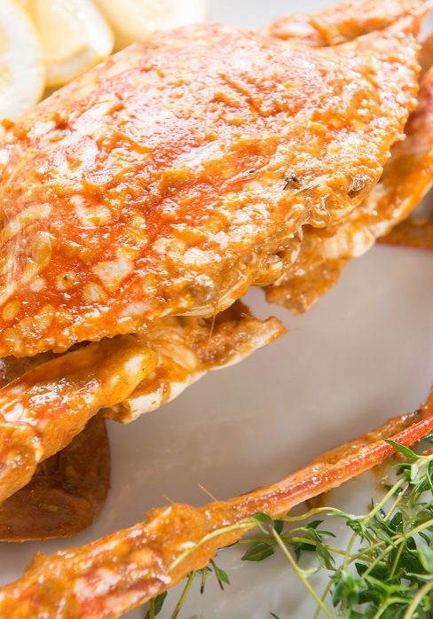 Close up cooked delicious hot and spicy sauce blue crab, on white plate. Fresh cook with hot smoke steams.