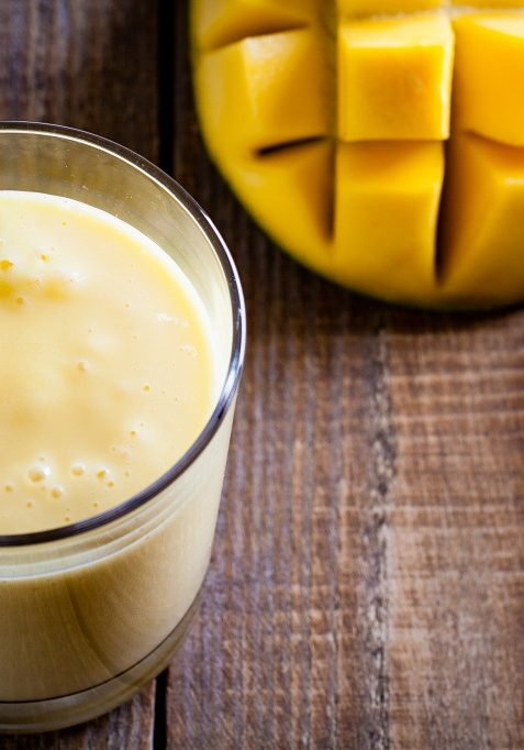 Glass of mango lassi, Indian drink made from yogurt with blended mango and honey, flavored with cardamom.
